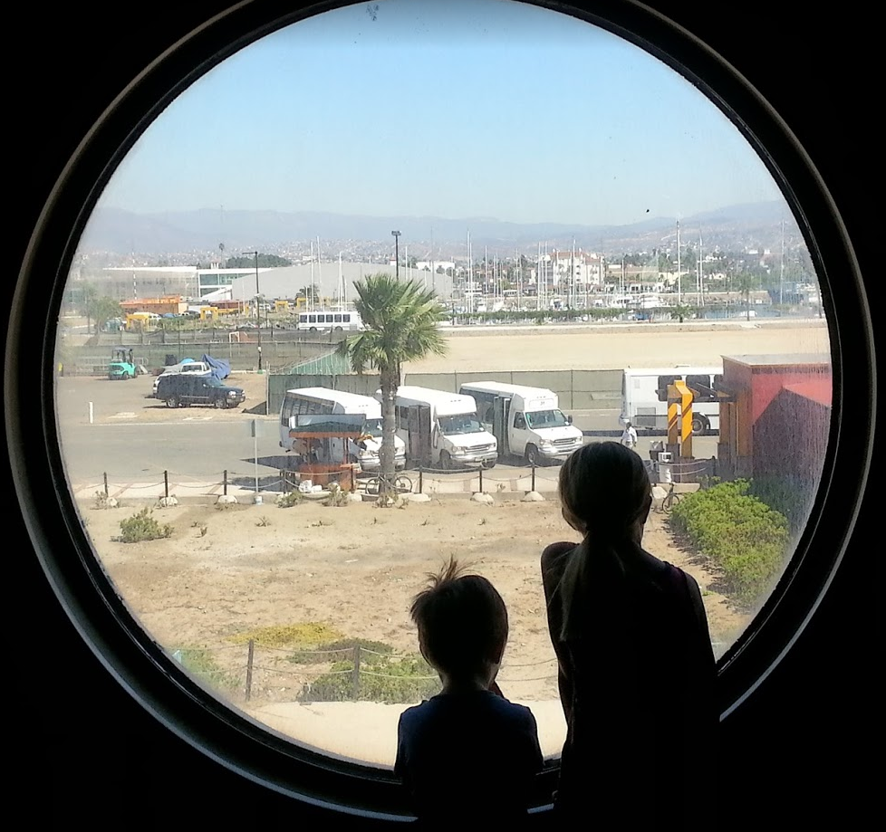 Kids looking out the cruise ship porthole in Ensenada.